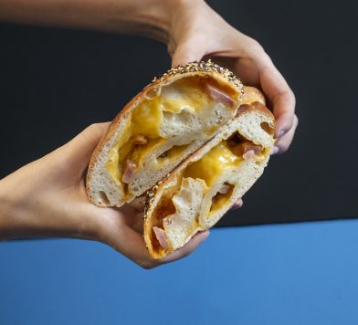 Two hands holding up cheesy bread