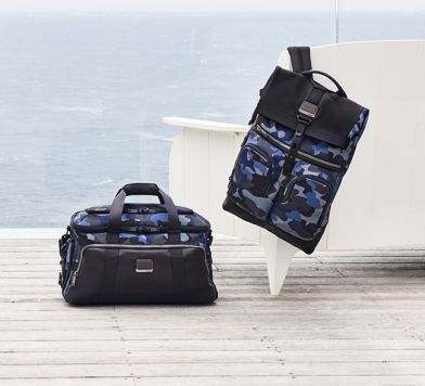 One blue and black duffle bag and one blue and back book bag on the floor