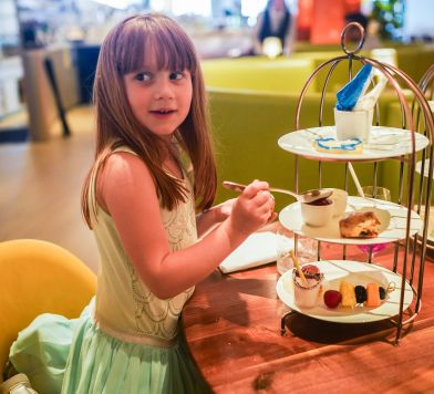 Little girl with long hair at a table with tea and macaroons