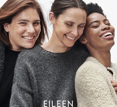 Three women laughing and wearing sweaters and laughing