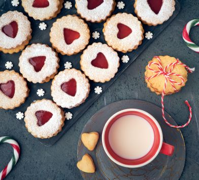 Top view of traditional Christmas Linzer cookies with red jam on dark background decorated with snowflakes and candy canes. These are traditional Austrian filled bisquits