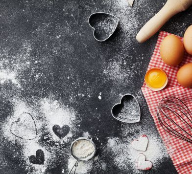 Baking background with flour, rolling pin, eggs, and heart shape on dark kitchen table top view for Valentines day cooking. Flat lay style.
