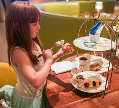 Little girl having tea and pastries at Bluebird London
